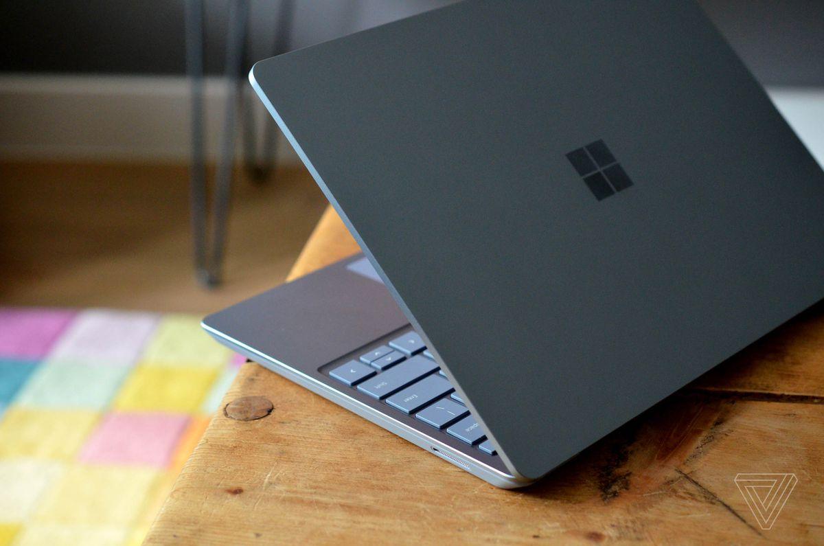Laptopul Surface merge pe colțul unei mese pe jumătate deschis, văzut din spate.