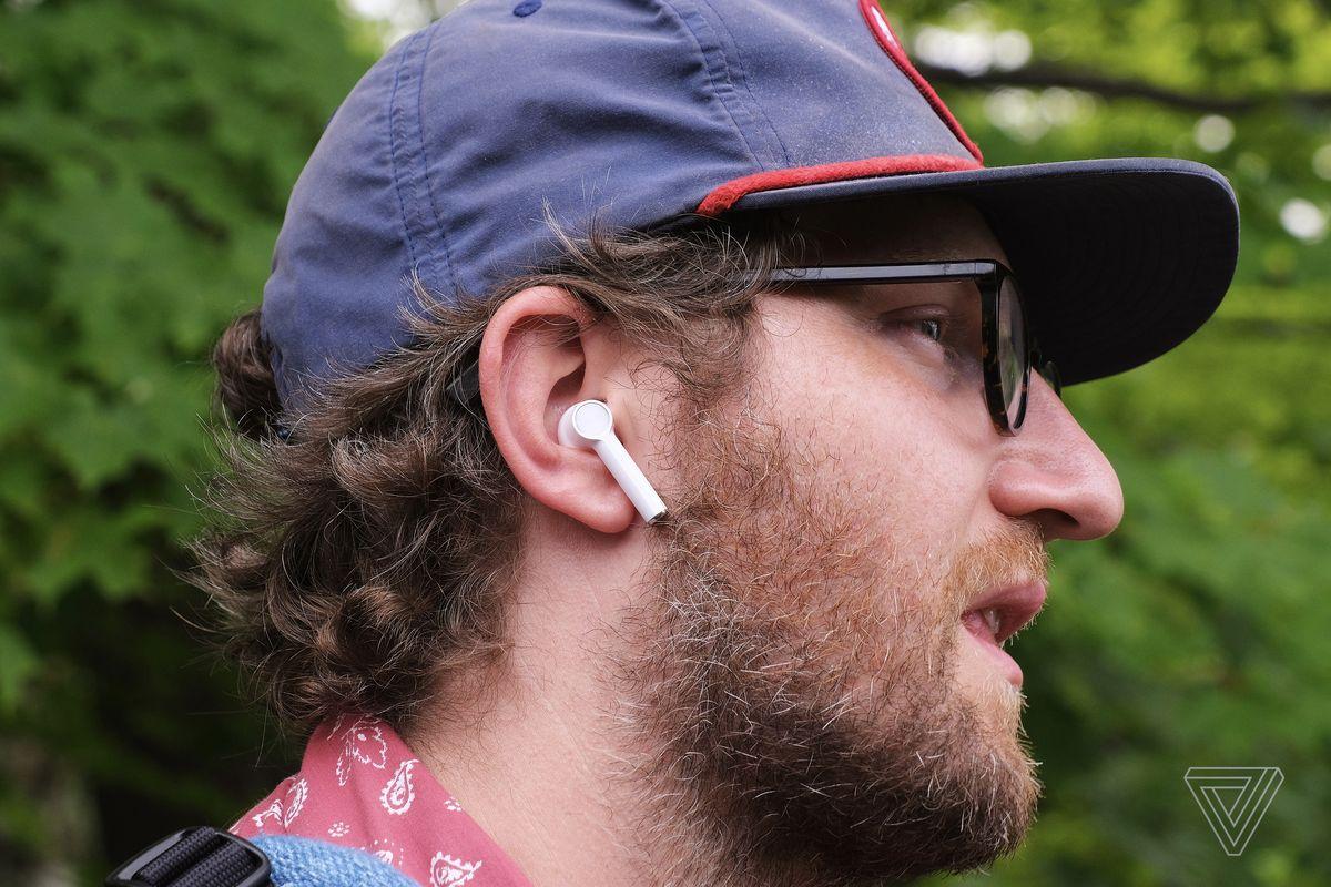 O persoană care poartă căștile OnePlus Buds.