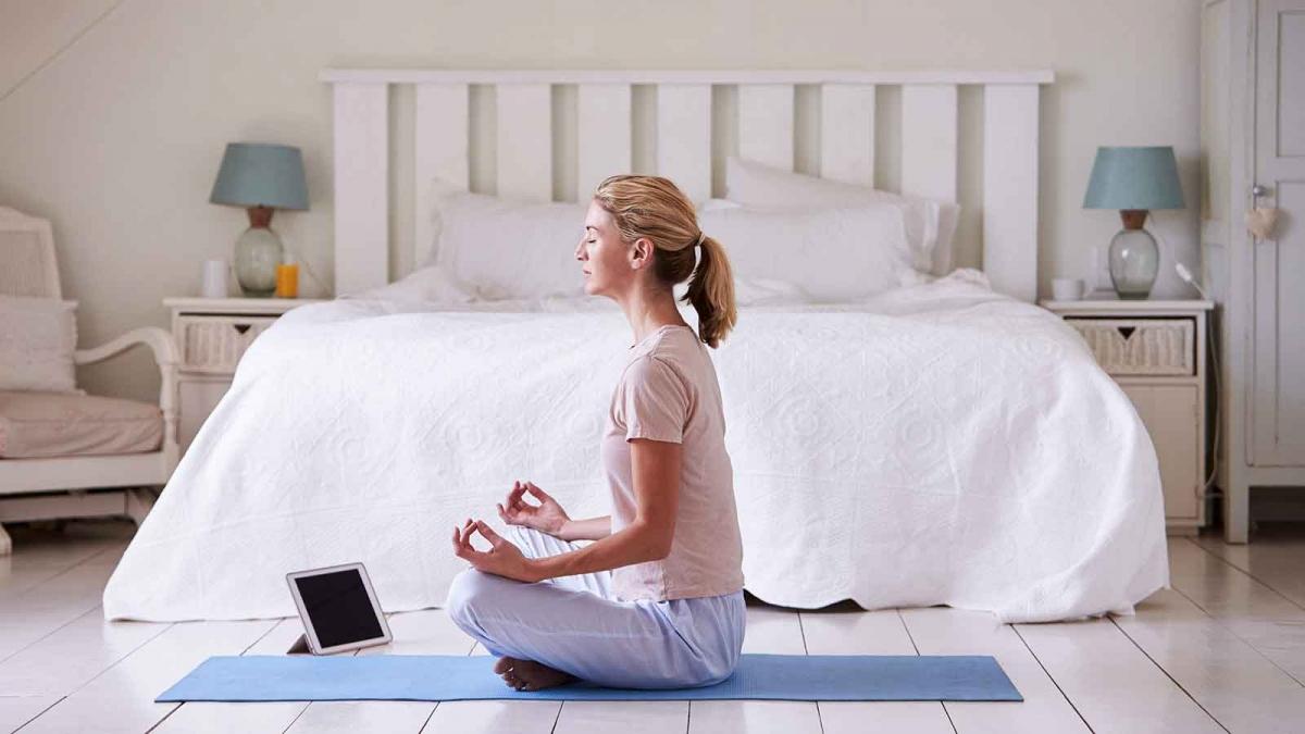 Femeie care meditează în dormitorul ei folosind o aplicație de meditație de pe iPad