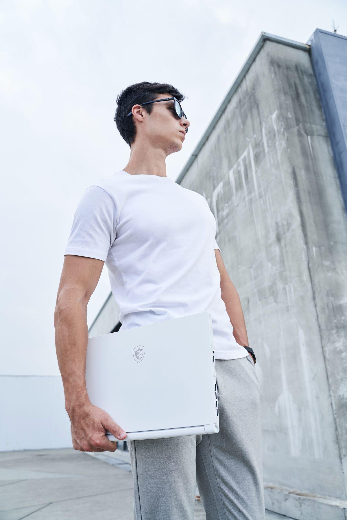 Un utilizator stă pe acoperișul unei clădiri purtând un tricou alb, ochelari de soare și pantaloni de trening.  Ei poartă un MSI Stealth 15M alb sub brațul drept în timp ce privesc spre stânga.