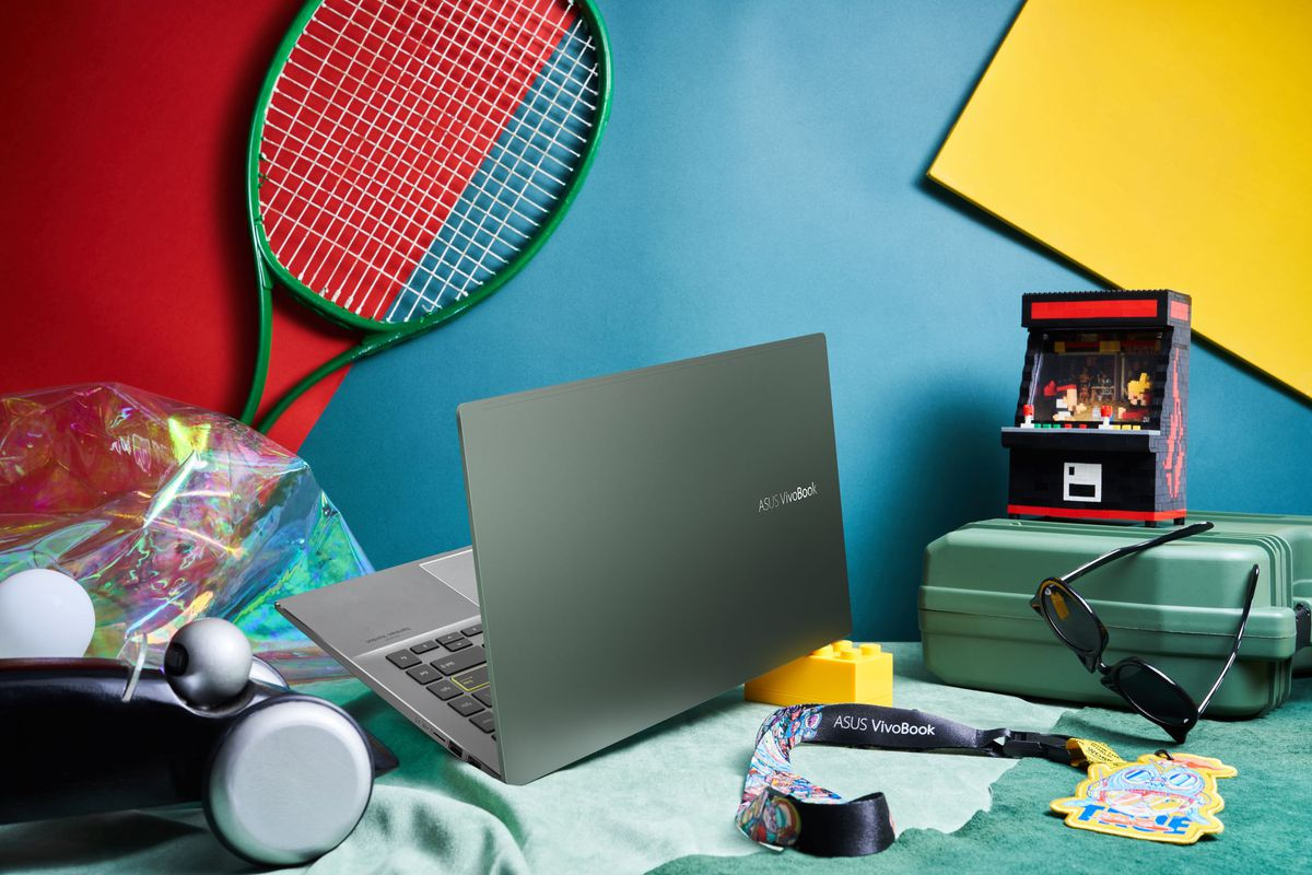 VivoBook S14, deschis, se îndreaptă spre cameră, lângă o grămadă de accesorii, inclusiv o rachetă de tenis, o cutie de instrumente și o pereche de ochelari de soare.