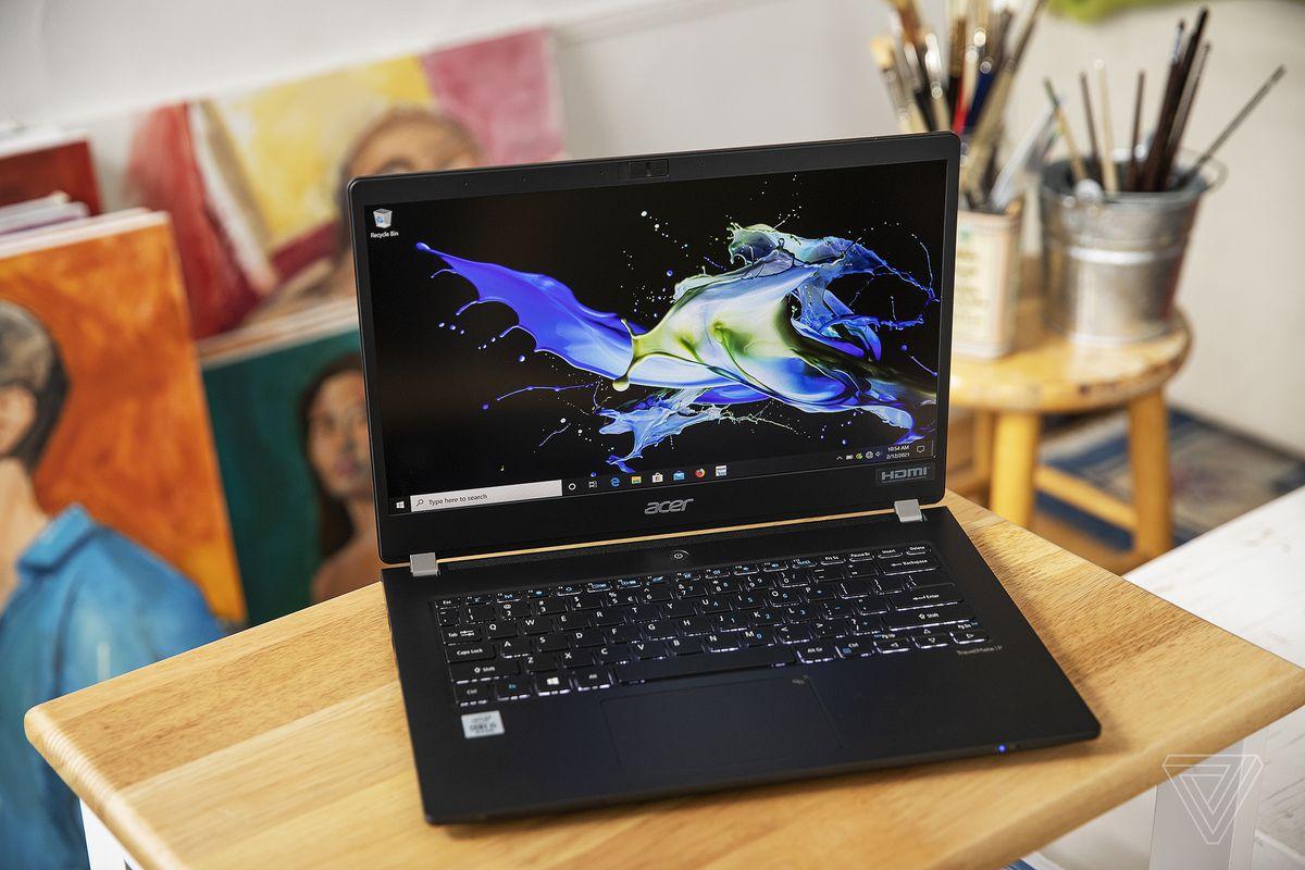 Acer Travelmate P6 pe o măsuță deschisă, înclinată ușor spre dreapta, văzută de sus.  Ecranul afișează un model verde și galben pe un fundal negru.