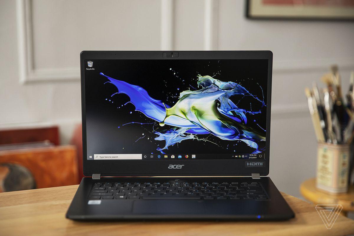 Acer Travelmate P6 văzut deschis din față.  Ecranul afișează un model albastru și galben pe un fundal negru.