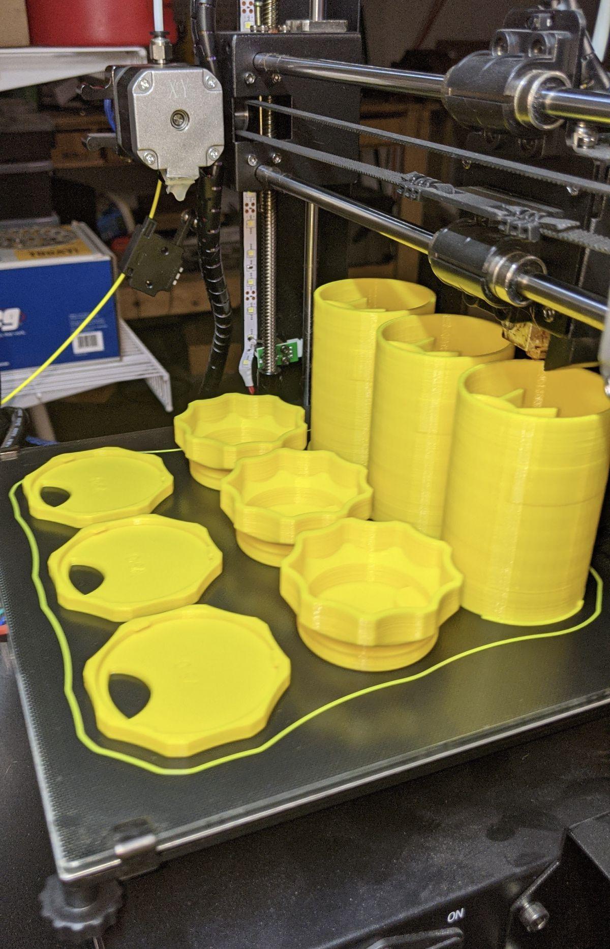 Trei corpuri de sticle galbene, trei capace și trei baze așezate pe o imprimantă 3D.