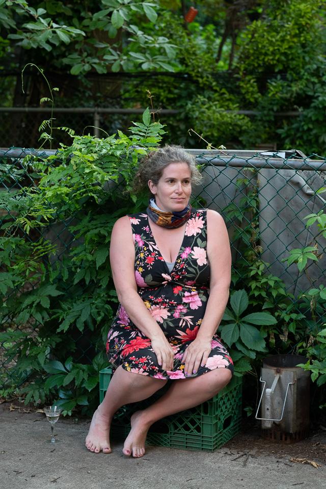 O femeie însărcinată într-o rochie florală fără mâneci stă pe o ladă verde lângă un gard cu plante verzi care o înconjoară.