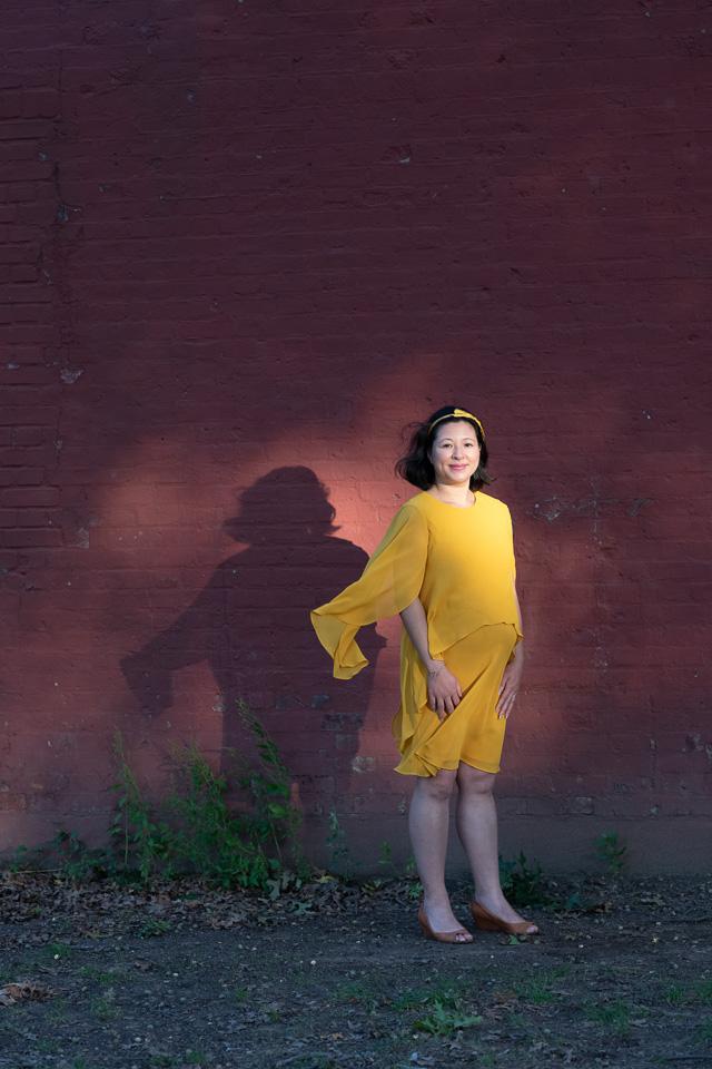 O femeie însărcinată care poartă o rochie galbenă stă în aer liber, într-o lumină caldă, împotriva unui perete de cărămidă roșie.