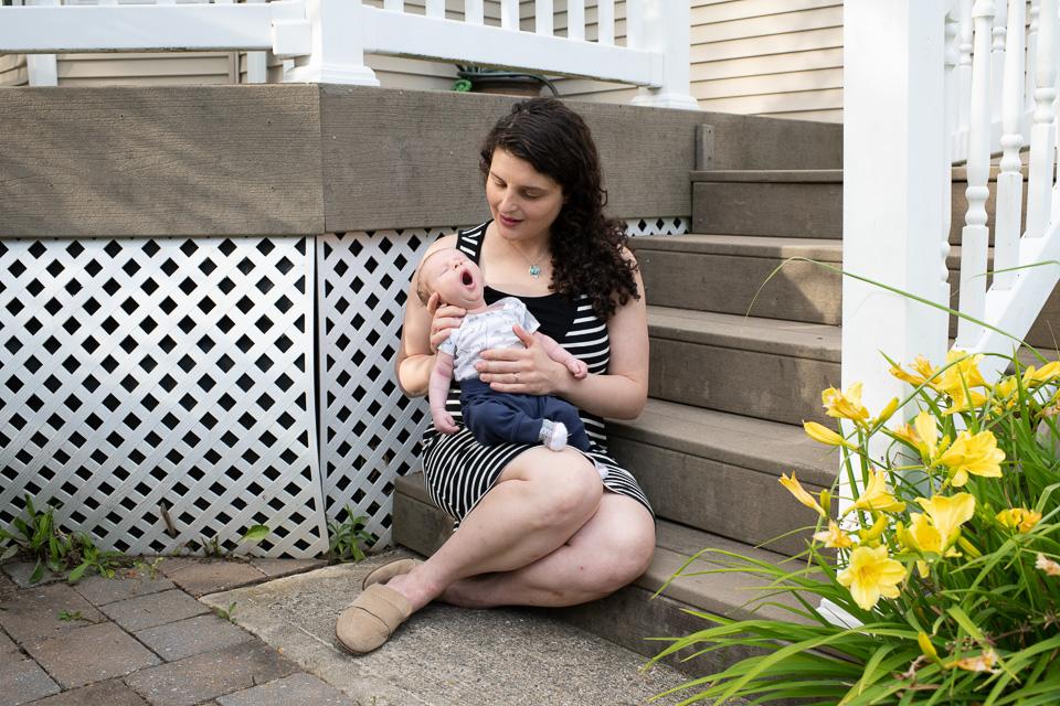 O femeie într-o rochie cu dungi stă în partea de jos a treptelor pridvorului ținând în poală un bebeluș mic, căscat.