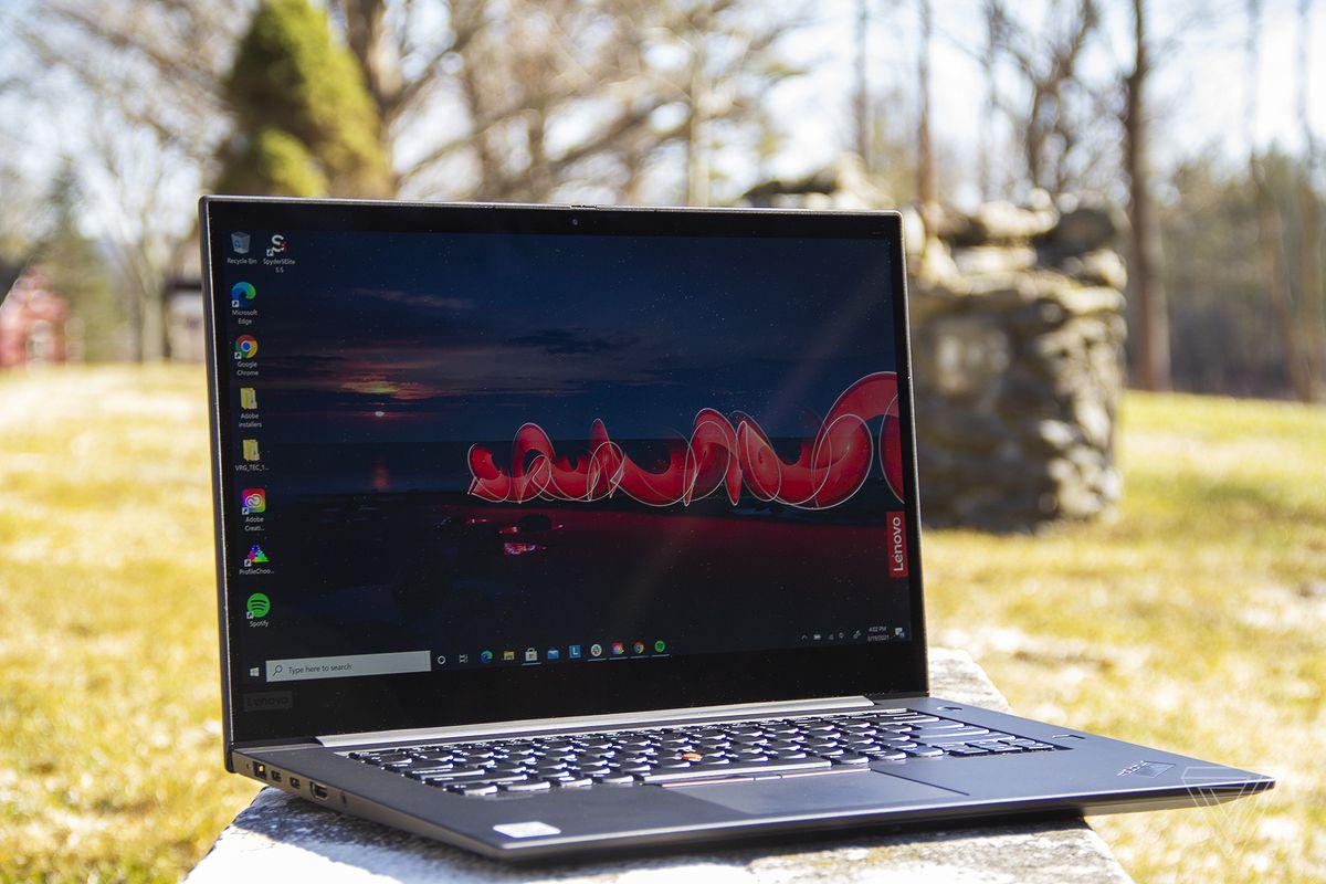 Lenovo Thinkpad X1 Extreme Gen 3 înclinat ușor spre dreapta, deschis.  Ecranul afișează o scenă de noapte în aer liber, cu sigla Lenovo în dreapta.