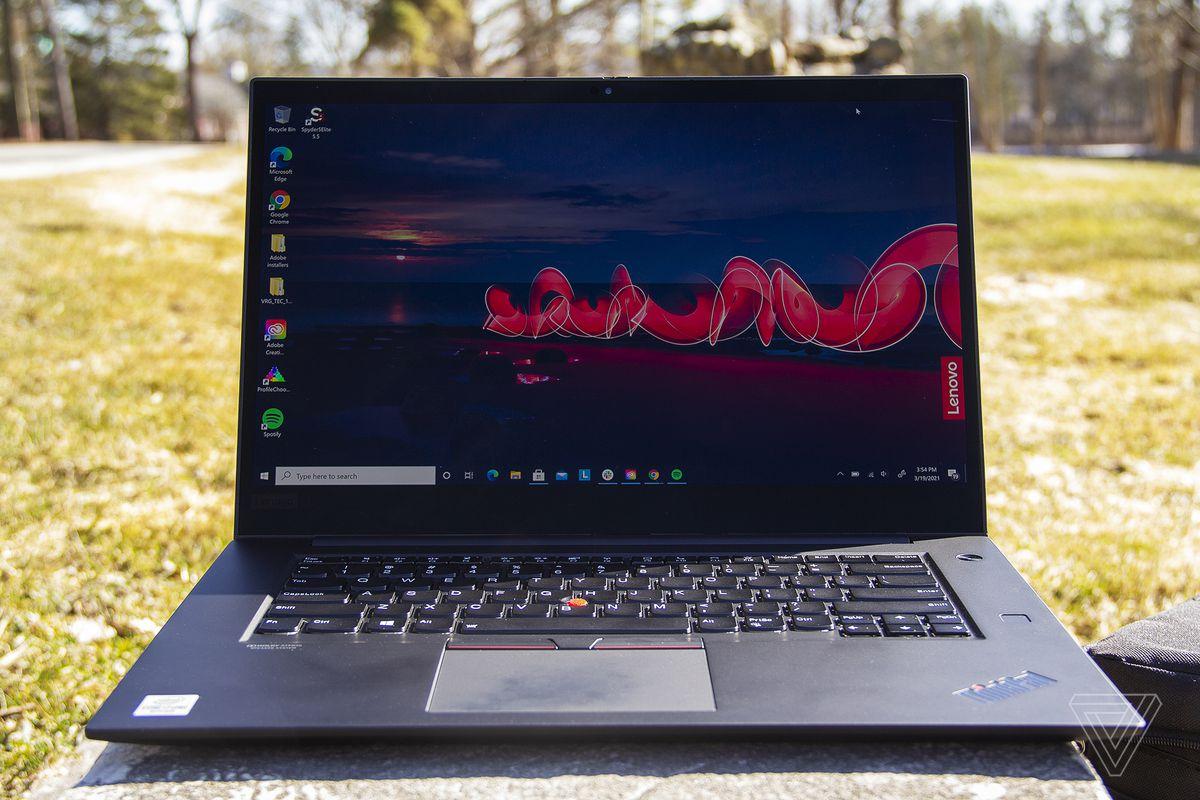Thinkpad X1 Extreme Gen 3 se deschide pe o placă de piatră în aer liber.  Ecranul afișează o scenă de noapte în aer liber, cu sigla Lenovo în partea dreaptă.