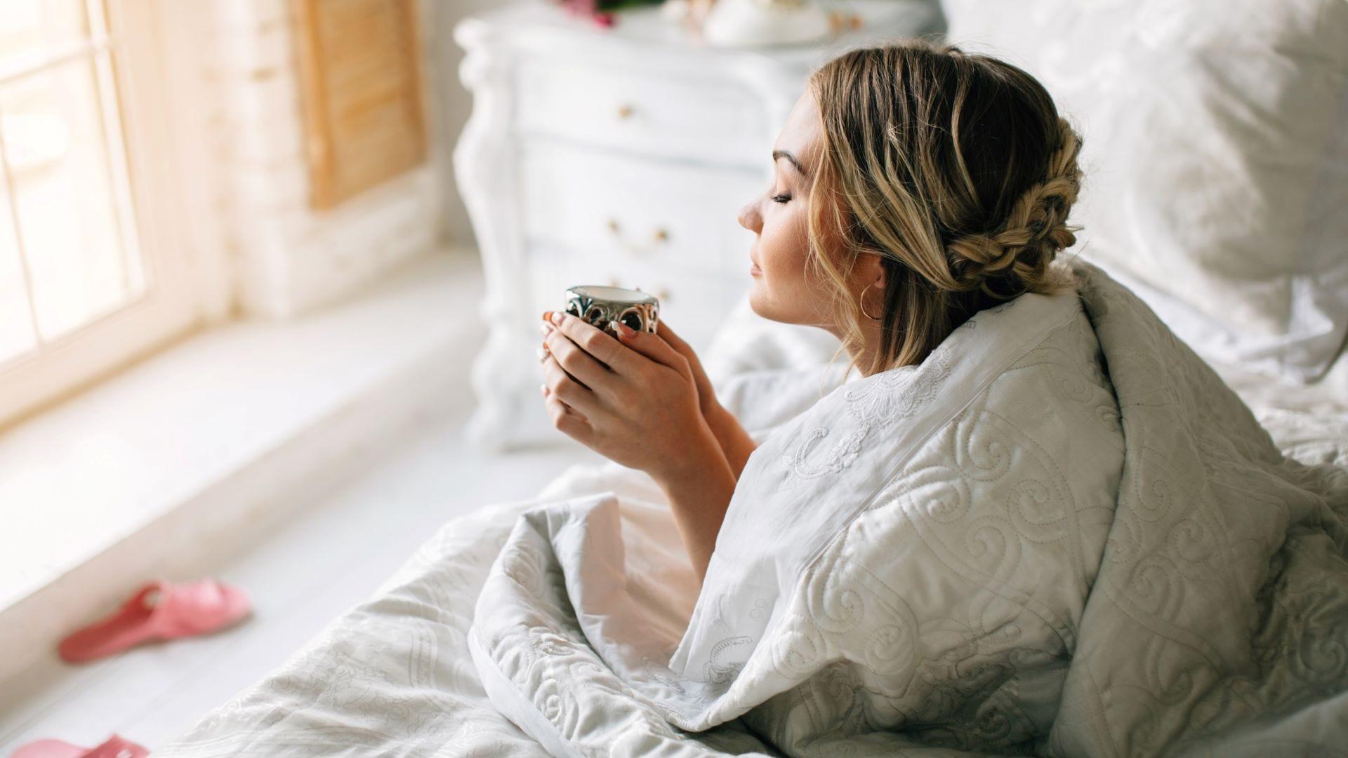 O femeie care bea cafea în pat dimineața.