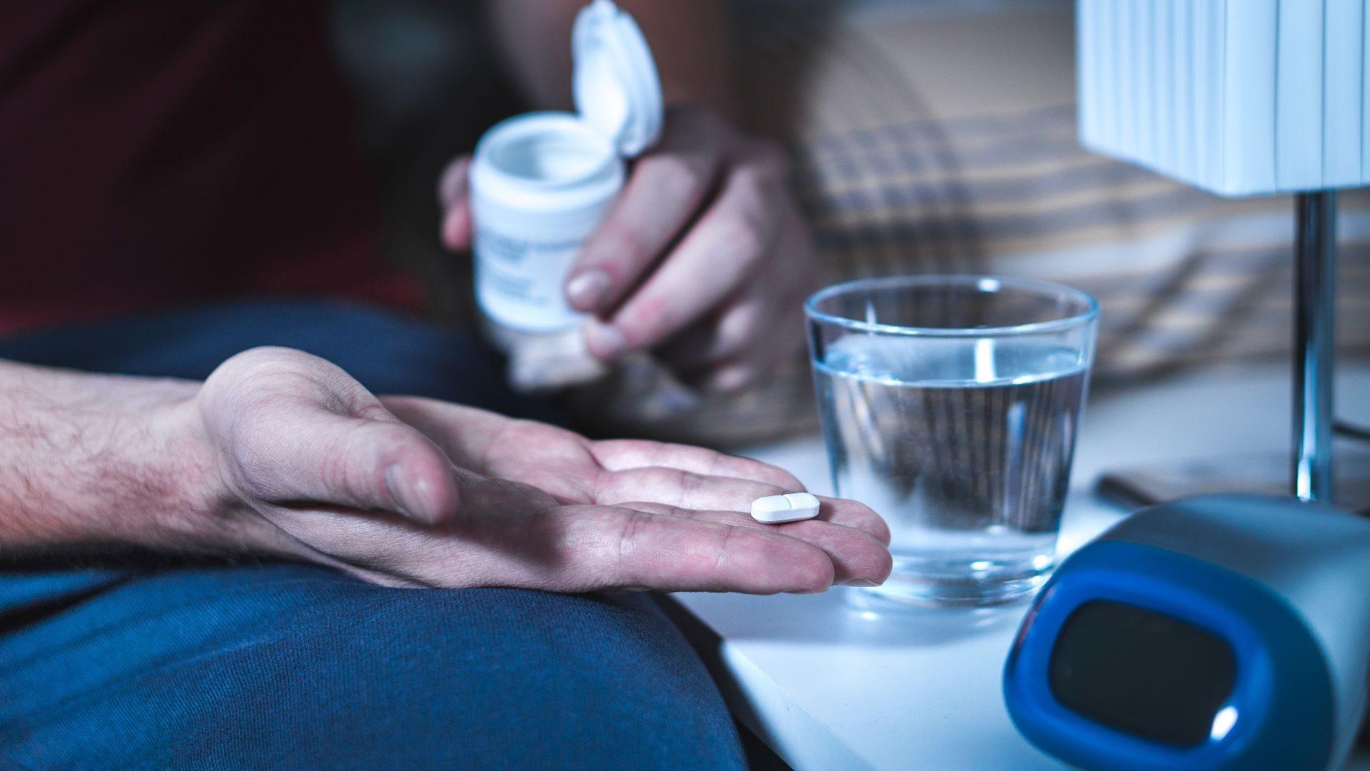 Un bărbat care ia o pastilă de melatonină înainte de culcare.