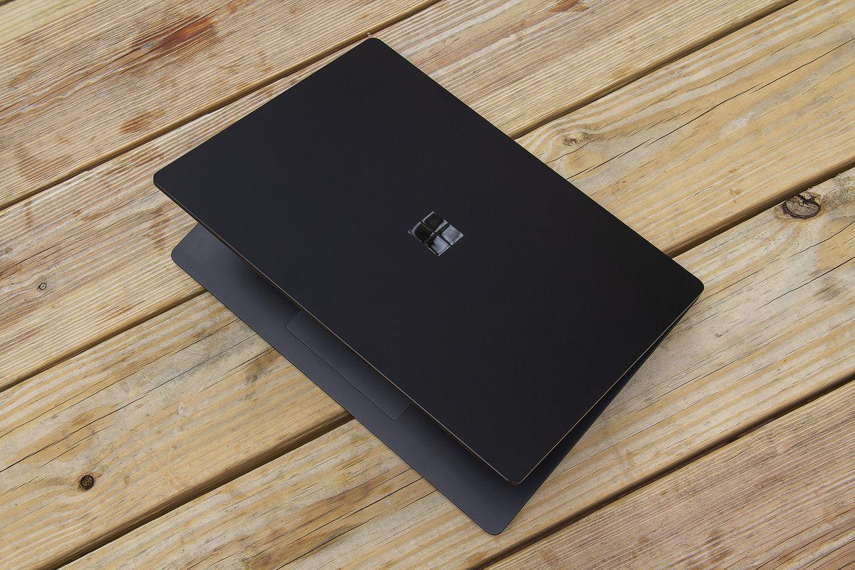 Laptopul de suprafață de 15 inci 4 pe jumătate deschis pe o masă de picnic, văzut de sus.