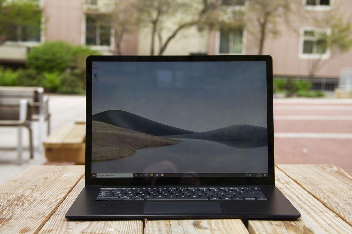 Laptopul Surface 4 de 15 inci se deschide pe o masă de picnic cu o clădire de apartamente roz în fundal.  Ecranul afișează dune de nisip cu un cer albastru.
