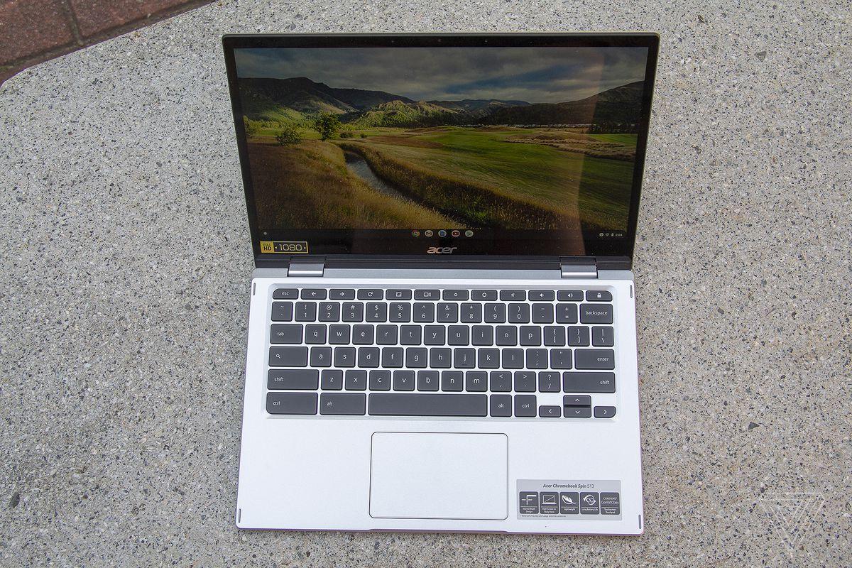 Chromebookul Acer Spin 513 pe o bancă de piatră, văzut de sus, deschis.  Ecranul afișează un peisaj pastoral.