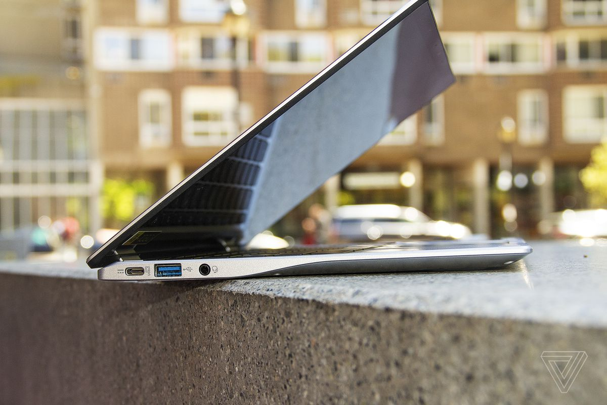 Chromebookul Acer Spin 513 văzut din stânga, pe jumătate deschis, pe o bancă de piatră.  O clădire de apartamente se află în fundal.