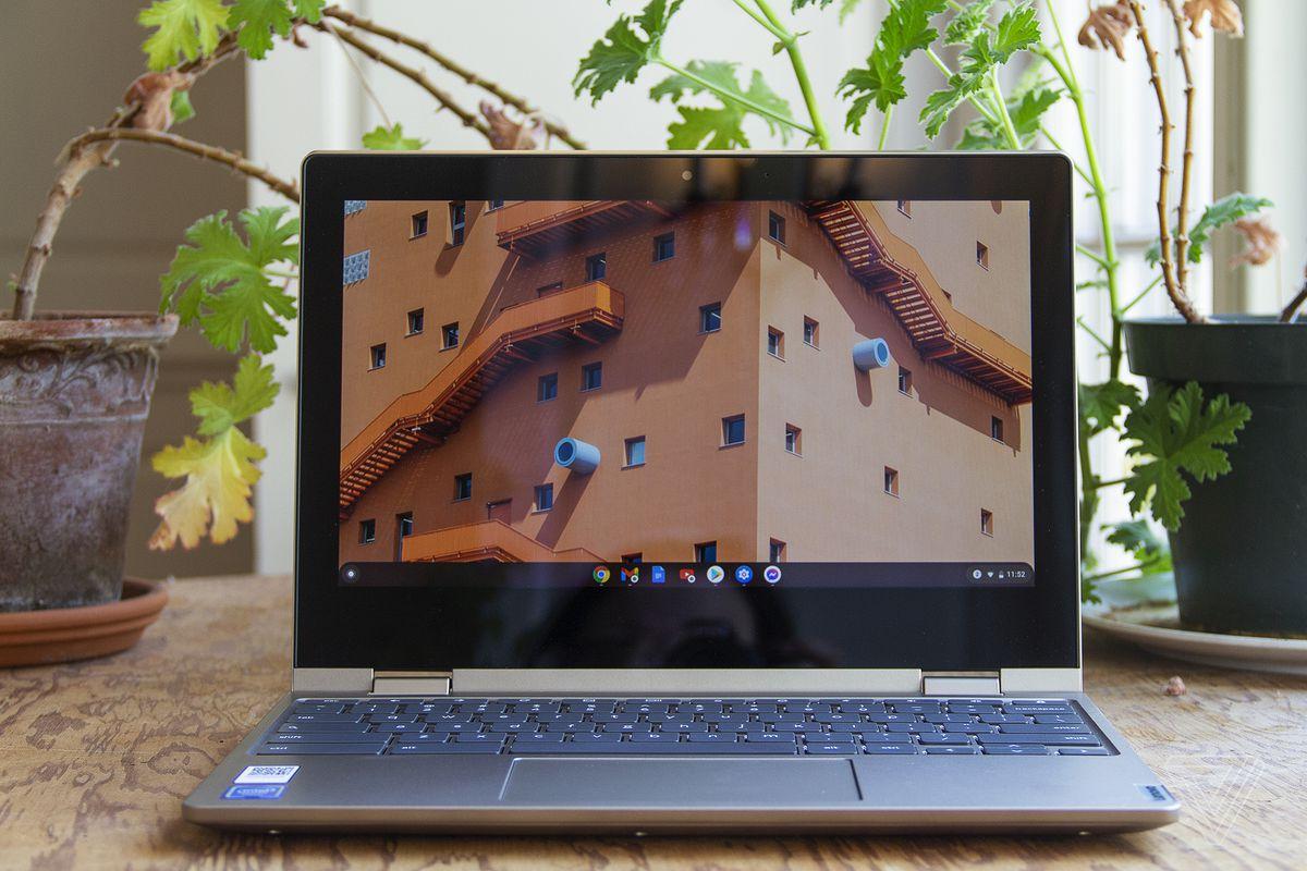 Chromebookul Lenovo Ideapad Flex 3 stă deschis pe o masă în fața a două plante de apartament.  Ecranul afișează ferestrele superioare ale unei clădiri mari.