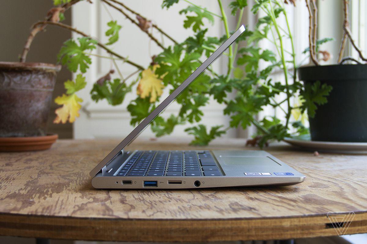 Chromebookul Lenovo Ideapad Flex 3 din partea stângă, pe jumătate deschis pe o masă în fața a două plante de apartament.