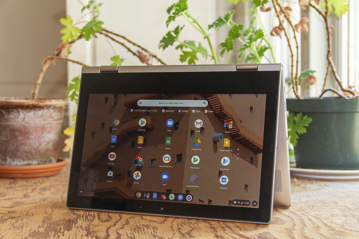 Chromebookul Lenovo Ideapad Flex 3 în modul cort, cu ecranul orientat spre cameră, înclinat ușor spre stânga, stă pe o masă cu două plante de apartament în fundal.  Ecranul afișează o grilă de pictograme ale aplicației Chrome OS.