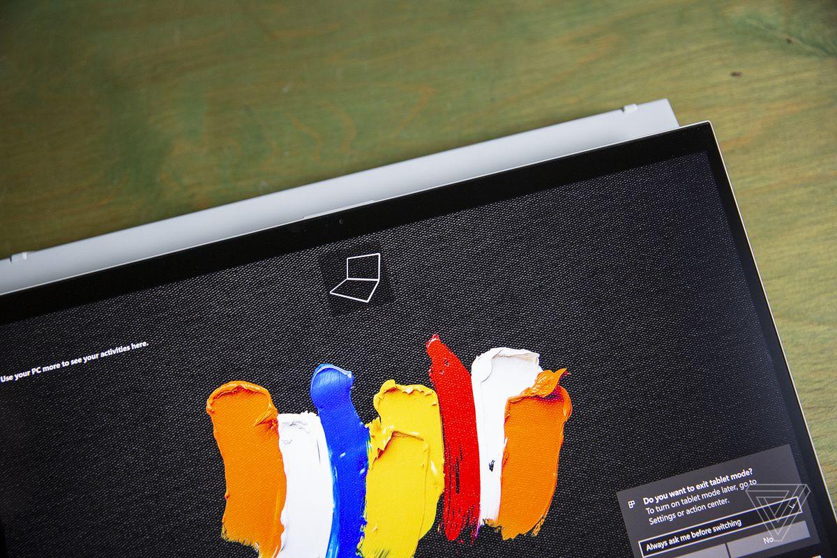 Acer ConceptD 7 Ezel cu ecranul plutind înapoi deasupra punții tastaturii, văzut de sus.  Ecranul afișează mai multe linii de vopsea multicolore pe un fundal negru.