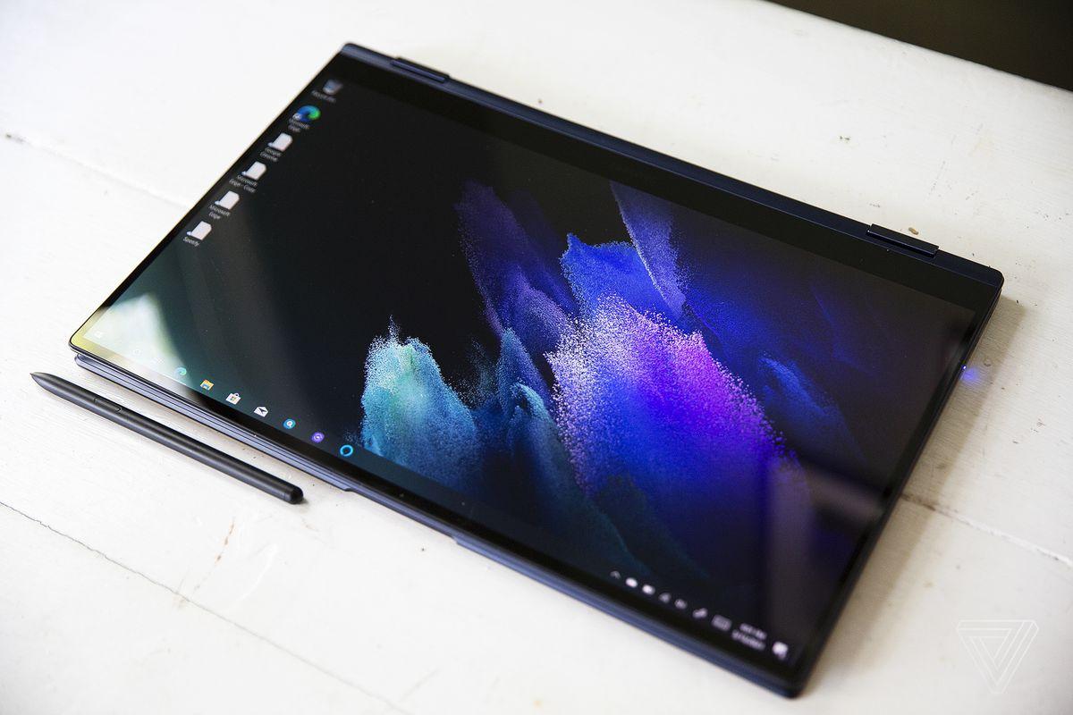 Samsung Galaxy Book Pro 360 (15 inci) în modul tabletă cu stylusul de sub el pe o masă albă.  Ecranul afișează un model pastel purpuriu pe un fundal întunecat.