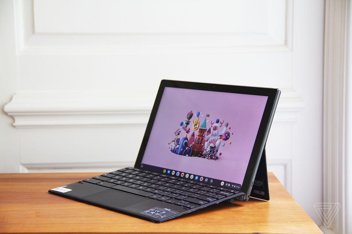 Asus Chromebook CM3 detașabil deschis, înclinat spre stânga.  Ecranul afișează o scenă de oraș cu desene animate pe un fundal roz.