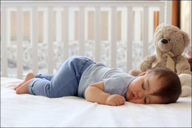 Copil care doarme în pătuț cu ursuleț de pluș