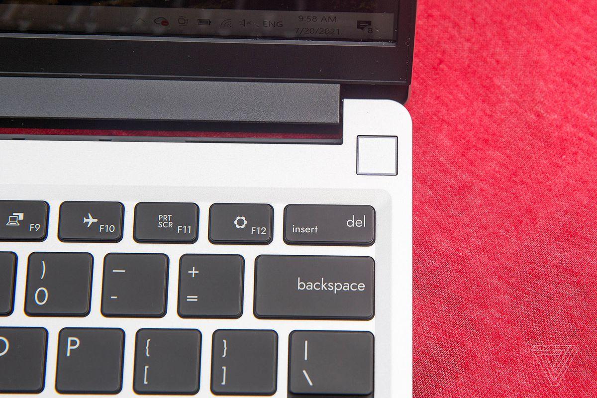 Senzorul de amprentă de pe laptop-ul Framework de pe o față de masă roșie.