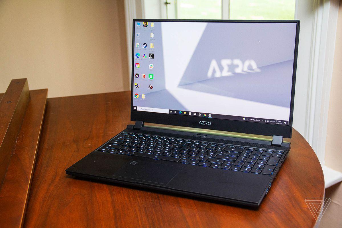 Gigabyte Aero 15 OLED se deschide pe un pian văzut de sus, înclinat spre stânga.  Tastatura este aprinsă în albastru deschis.  Ecranul afișează un desktop cu un fundal gri și alb.