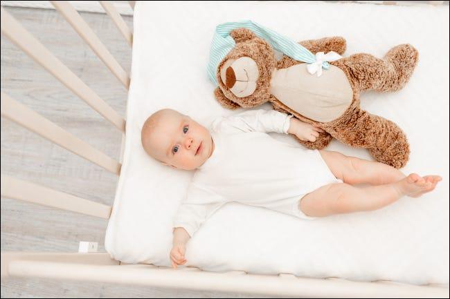 Bebeluș în pătuț cu ursuleț de pluș
