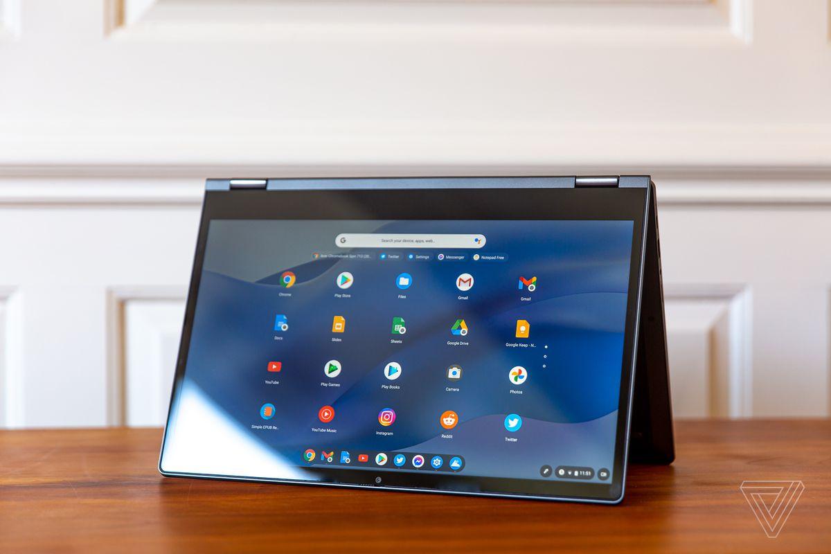 Chromebookul Lenovo Flex 5 în modul cort, înclinat spre stânga.  Ecranul afișează o grilă de pictograme Chrome OS pe un fundal ondulat albastru.