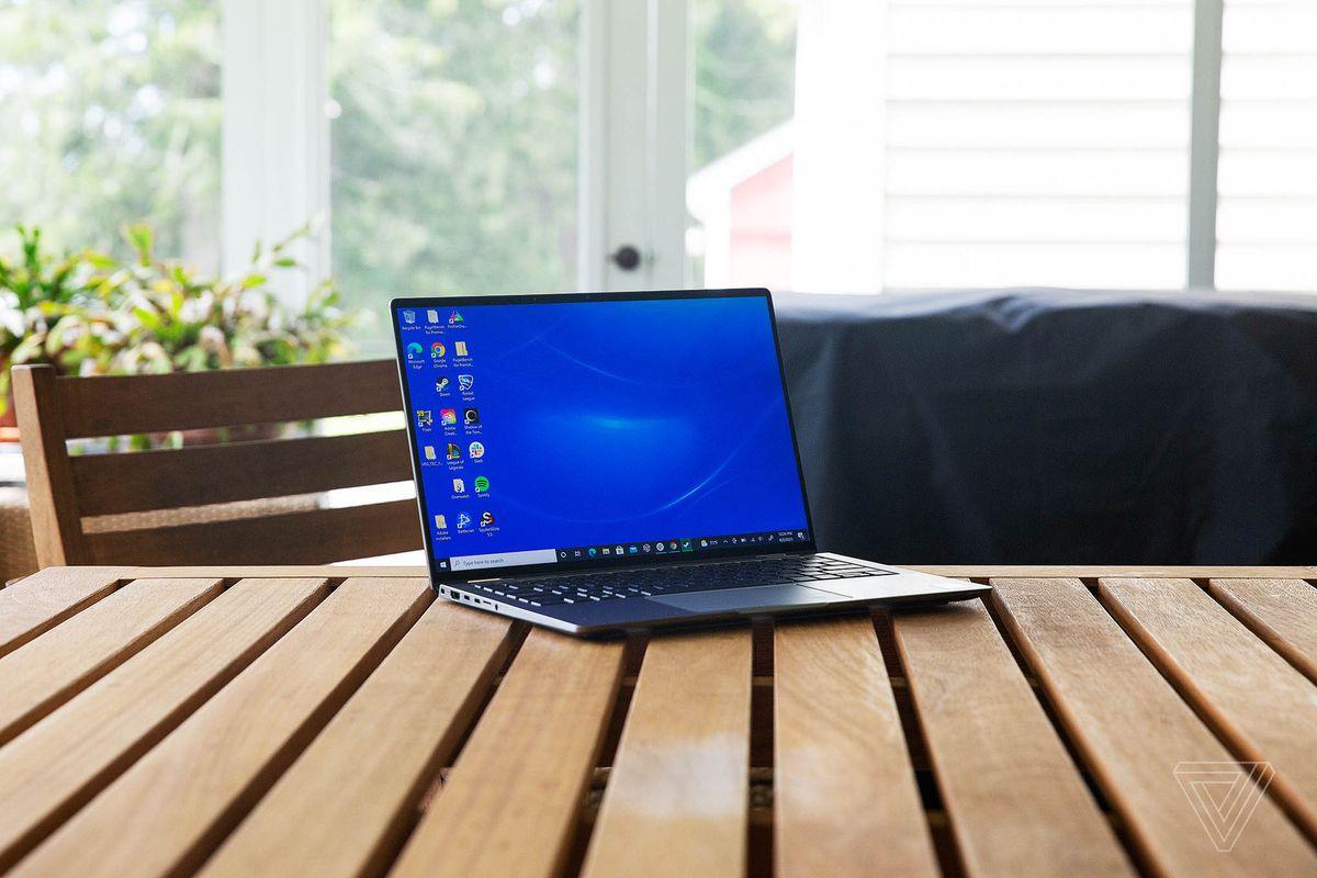 Dell Latitude 9420 pe o masă de lemn, deschisă, ușor înclinată spre dreapta.  Ecranul afișează un fundal albastru pentru desktop.