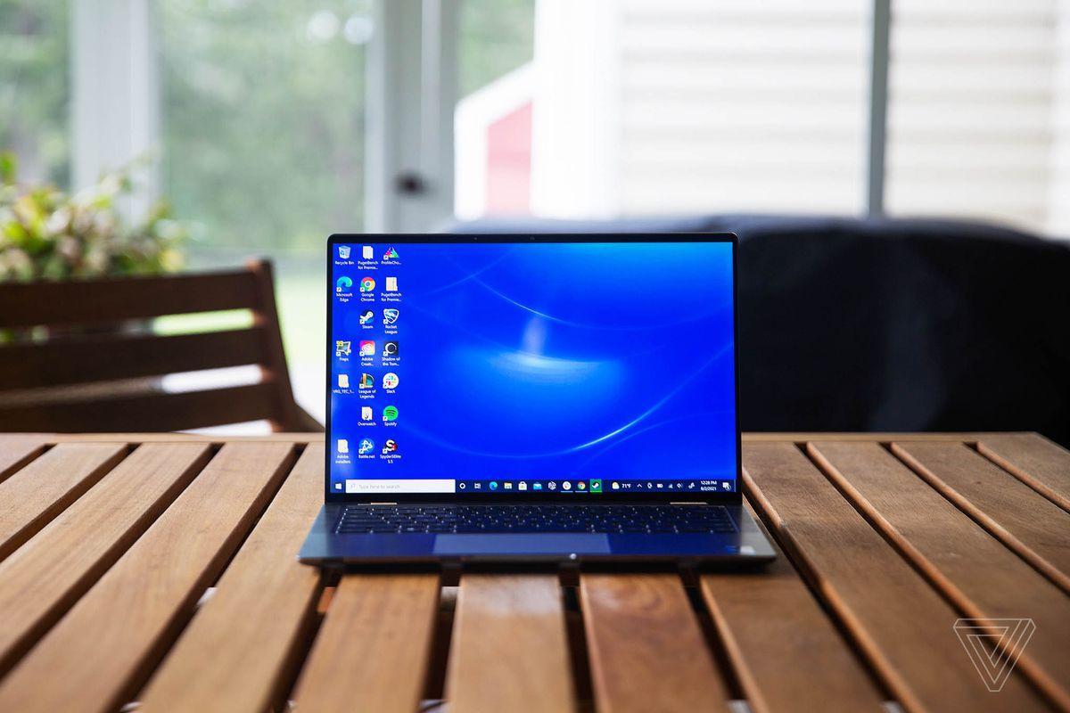 Dell Latitude 9420 se deschide pe o masă de verandă din lemn.  Ecranul afișează un fundal albastru pentru desktop.