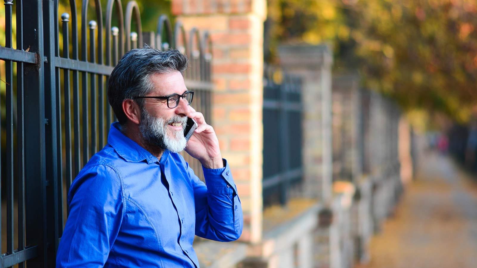 Un bărbat rezemat de un gard de fier, în timp ce vorbea la telefon.