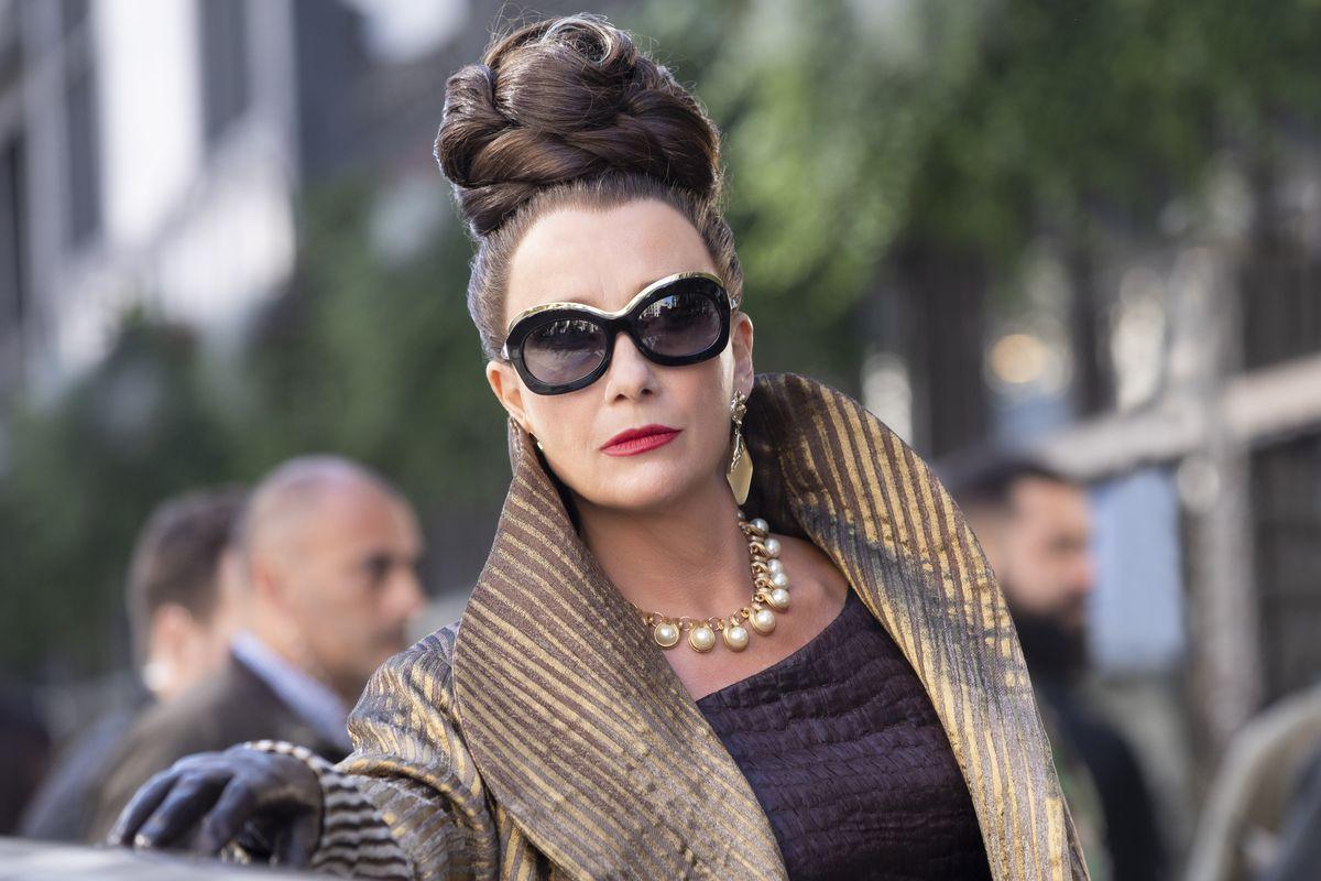 Emma Thompson ca baronă.  Părul ei este sus într-o coafură complicată, poartă ochelari de soare mari, cercei de aur, un colier de perle și o haină mare de aur.