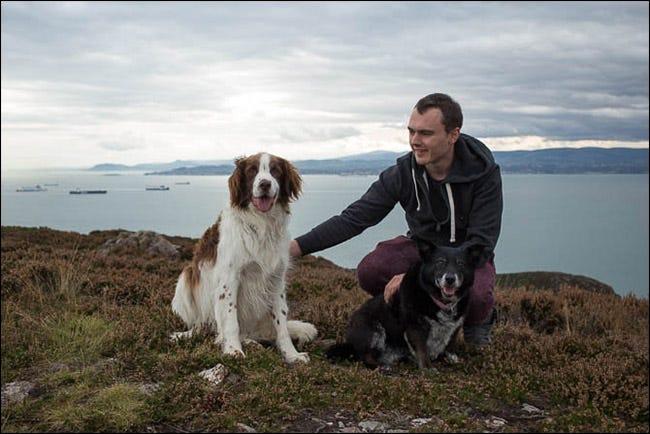 Un bărbat care ține cei doi câini calmi și pregătiți pentru fotografie