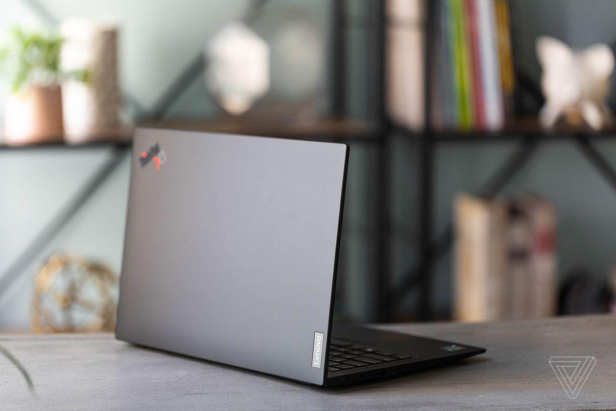 Lenovo ThinkPad X1 Carbon Gen 9 pe o masă în fața unui raft, cu fața în fața camerei, înclinat spre dreapta.