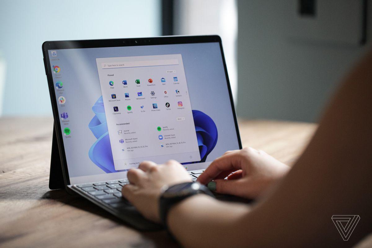 Un utilizator tastează pe Surface Pro 8 din spate.  Ecranul afișează meniul de pornire Windows 11 pe un fundal alb și albastru.