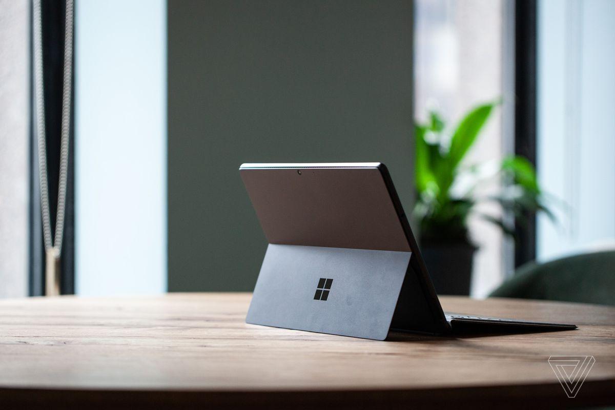 Surface Pro 8 de pe o masă văzută din spate spre dreapta, deschisă, cu tastatura semnată atașată și suportul afară.  În fundal este un perete verde și o plantă în ghiveci.