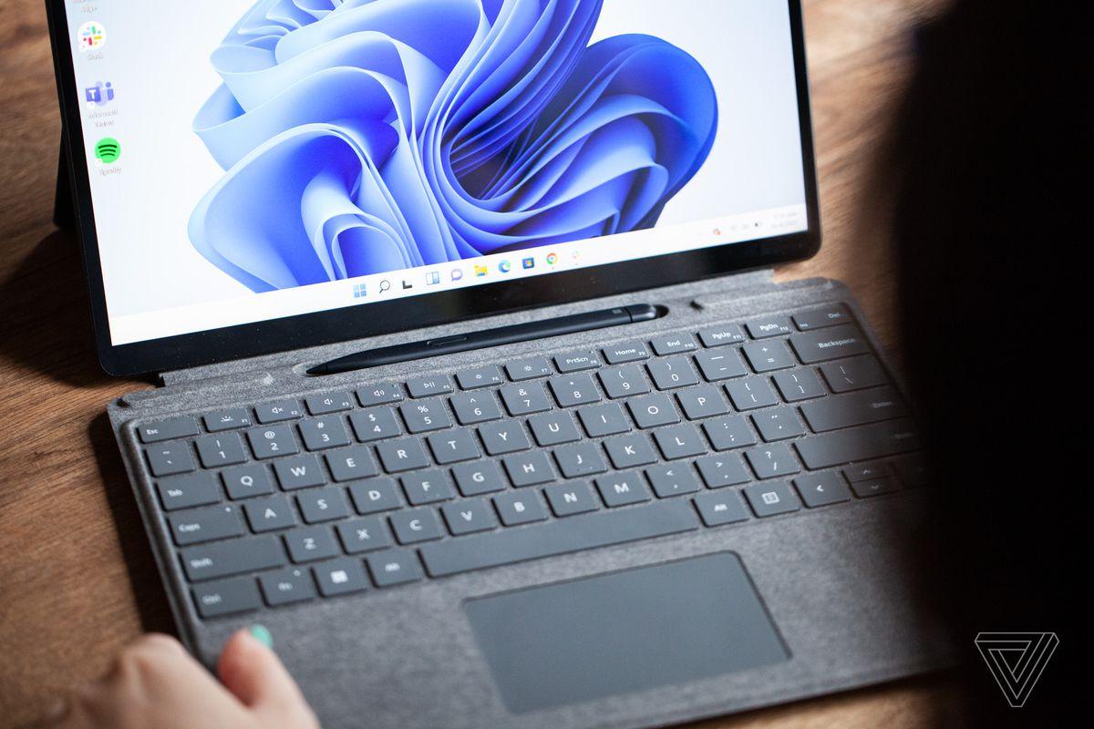 Surface Pro 8 este deschis, de aproape, cu tastatura scoasă și stiloul vizibil.  Ecranul afișează un vârtej albastru pe un fundal alb.