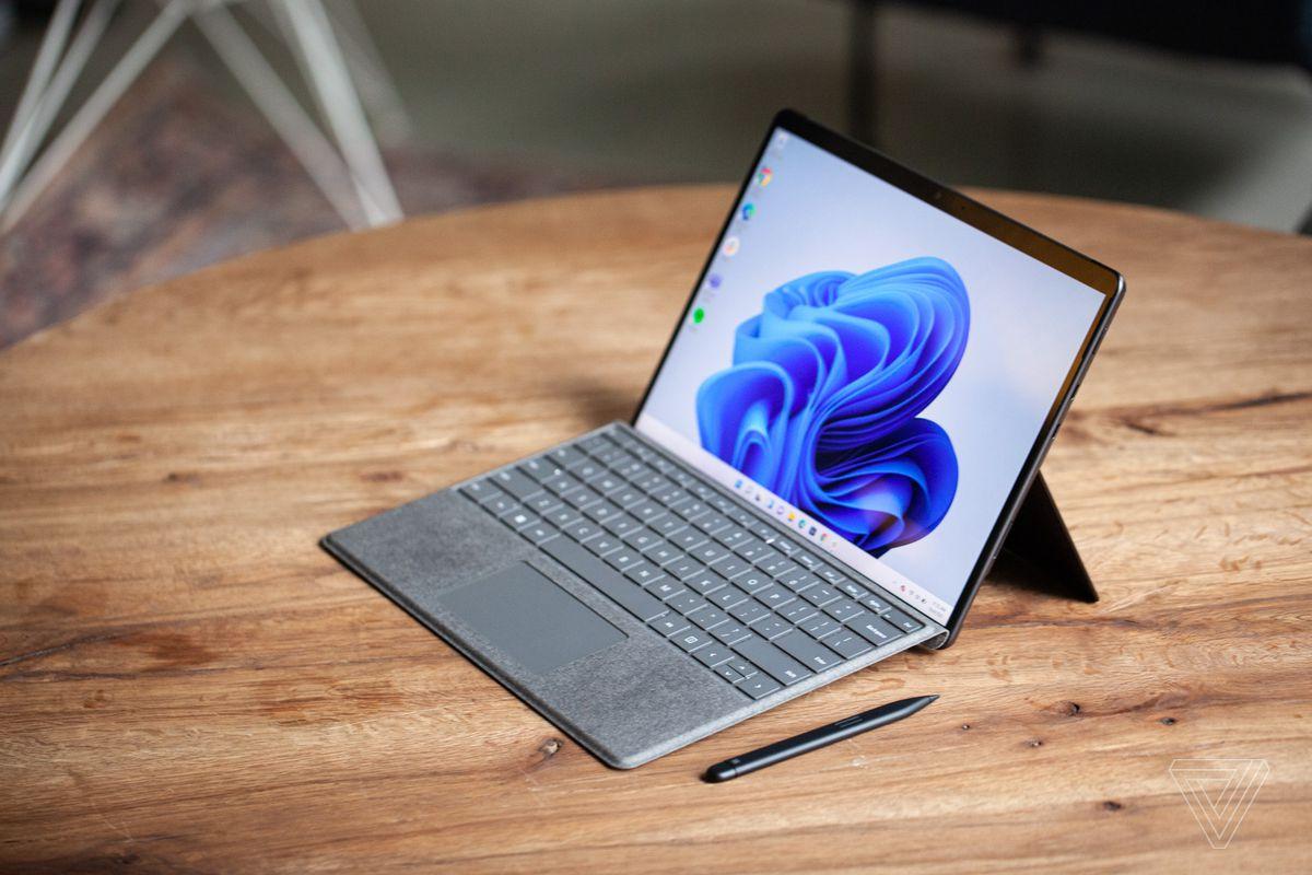 Surface Pro 8 văzut de sus și în dreapta pe o masă cu Surface Slim Pen 2 lângă acesta și tastatura cu semnătură atașată.  Ecranul afișează un vârtej albastru pe un fundal alb.