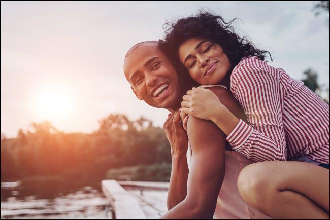 Un cuplu îmbrățișând și arătând fericit pe un doc de lac